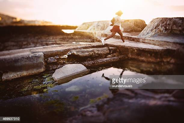 Teen hipster girl jumping over rock pool at the beach