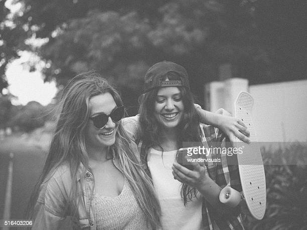 Teen hipster girls laughing at something on a mobile phone
