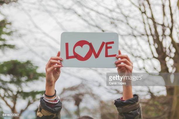 teen holding board with LOVE text