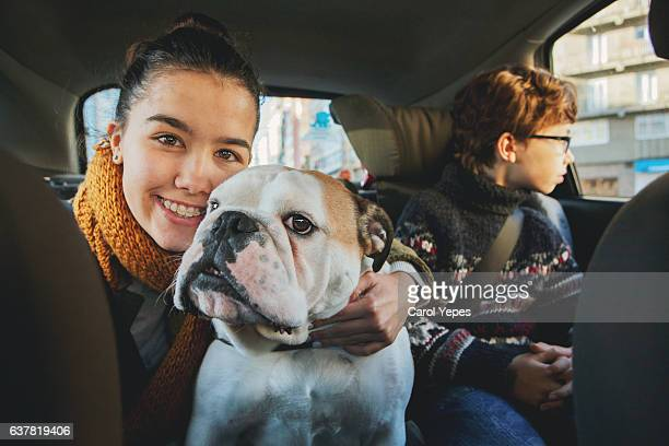 teen holding dog in a car