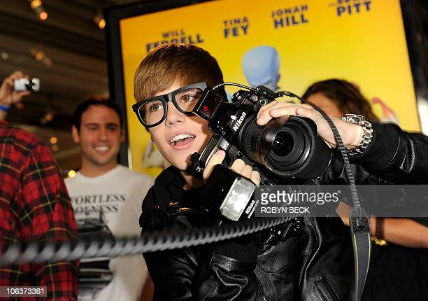 Teen idol Justin Bieber borrows a photographer's camera and takes some shots as he arrives at the Los Angeles premiere of the Dreamworks animated...