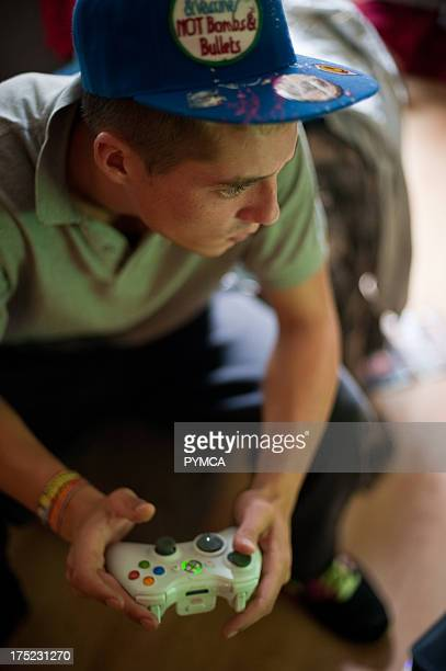 Teen in baseball cap with XBox controller in hands