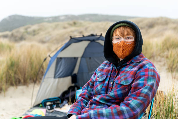 Teen in camp chair on the coast with mask looking at camera near dunes