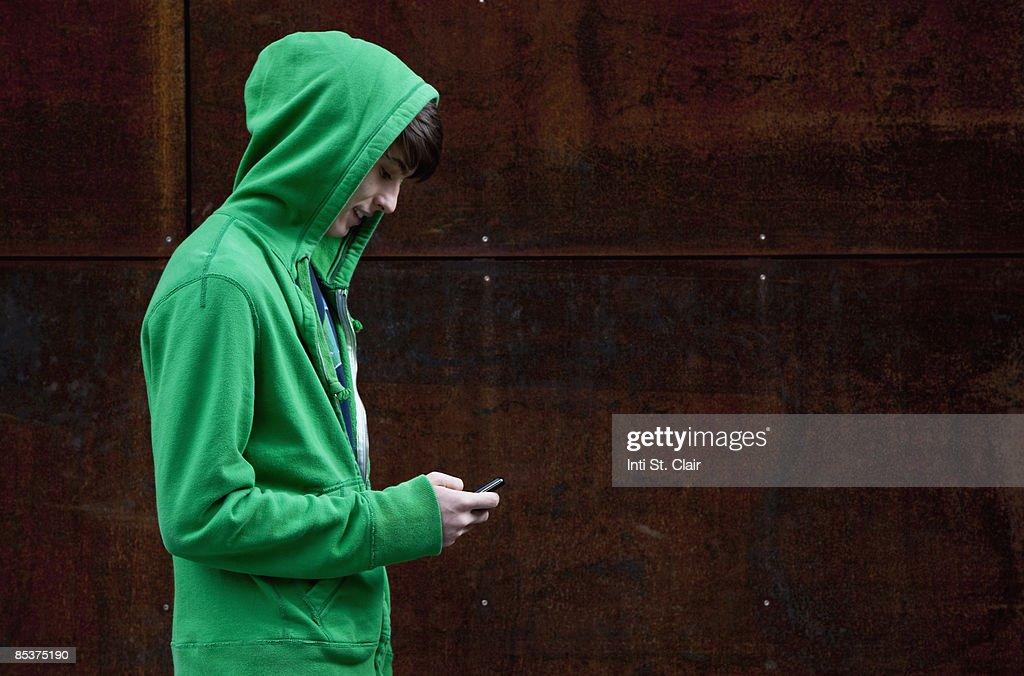 Teen in hooded sweatshirt text messaging : Stock Photo