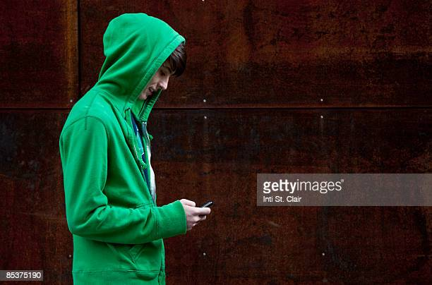 Teen in hooded sweatshirt text messaging