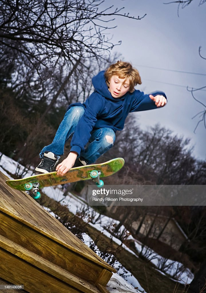 Teen jumping his skateboard off deck : Stock Photo