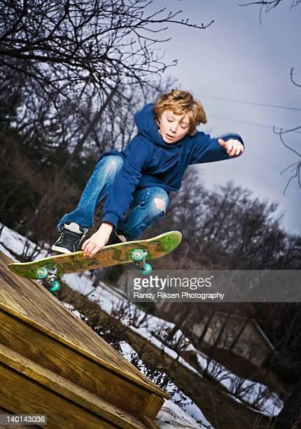 Teen jumping his skateboard off deck