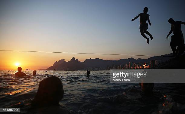 A teen jumps off the rocks at Arpoador at sunset on January 11 2015 in Rio de Janeiro Brazil Rio residents flocked to the beach this weekend as...