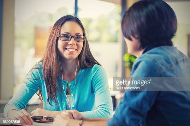 Teen listening to headphones at restaurant with mother