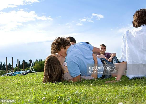 Teen lovers kissing in front of friends