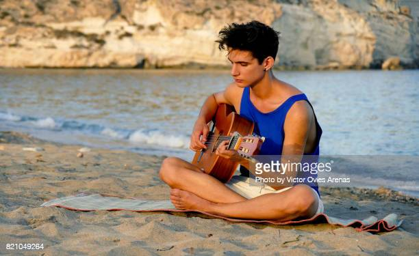 teen male model playing spanish guitar on the beach - victor ovies fotografías e imágenes de stock