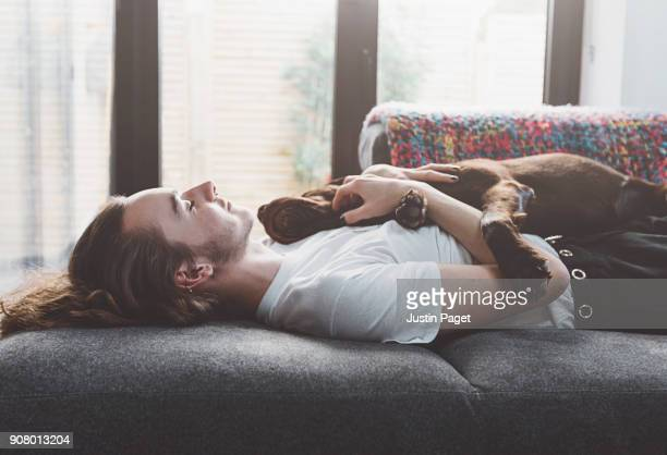 Teen napping on the sofa with dog