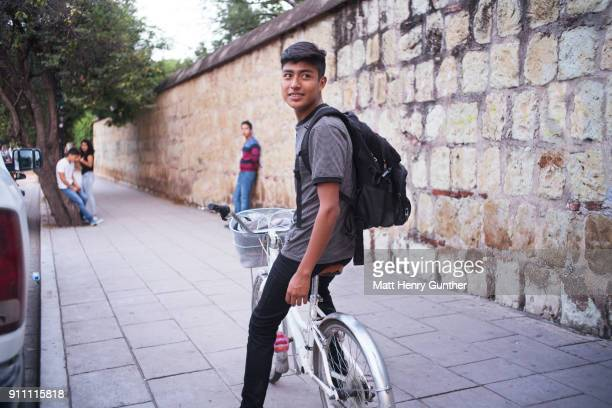 teen on bike looking over his shoulder with a backpack on against a rock tiled wall