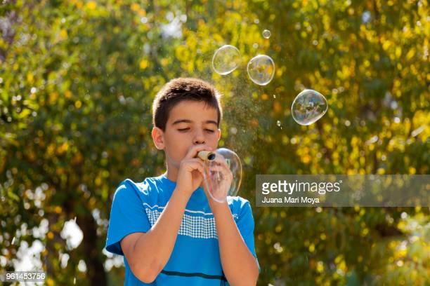 Teen playing with bubbles. With green background