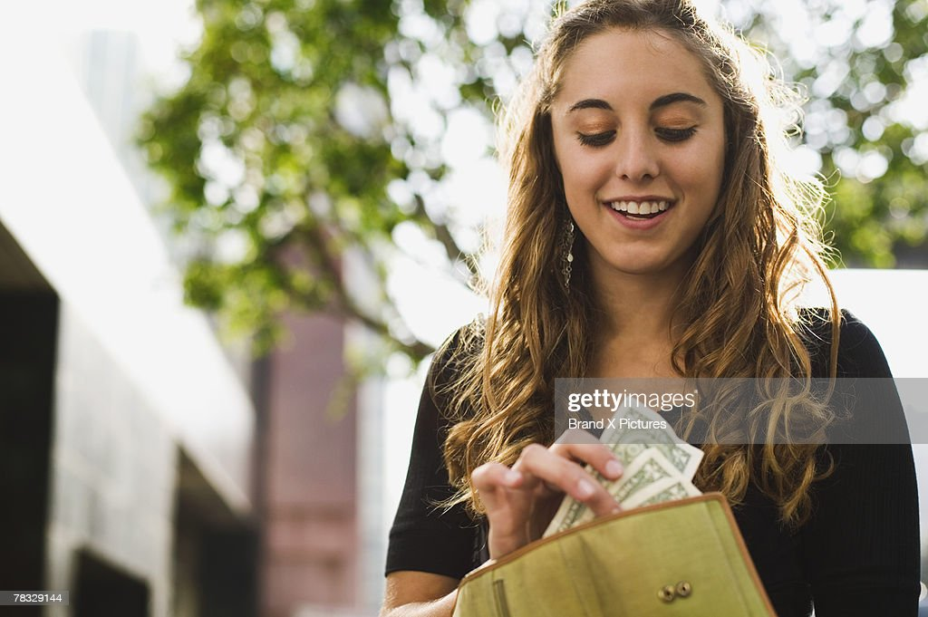 Teen removing money from wallet : Stock Photo