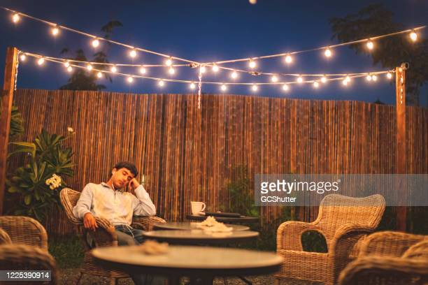 teen resting in the backyard patio listening to music - covid-19 series - fence stock pictures, royalty-free photos & images
