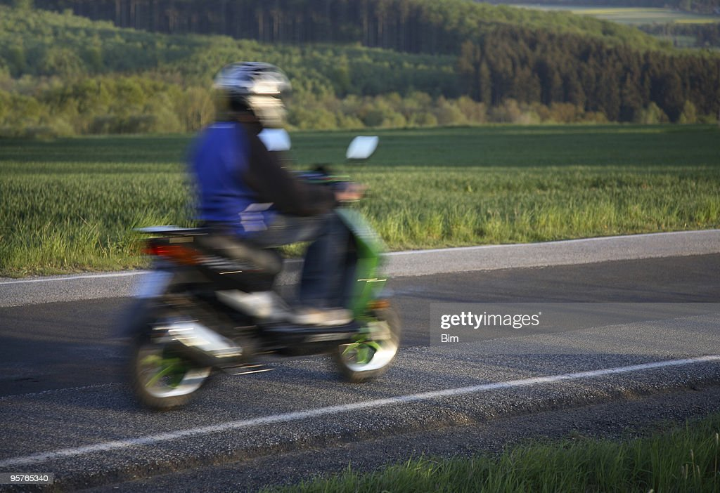 Teen riding home on his moped, motion blur : Stock Photo