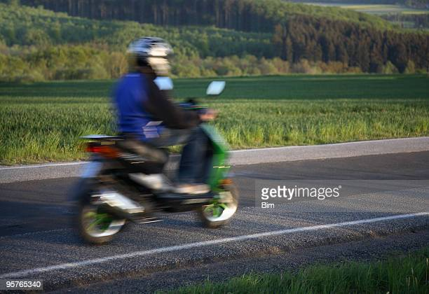 Teen riding Hause auf seinem moped, motion blur