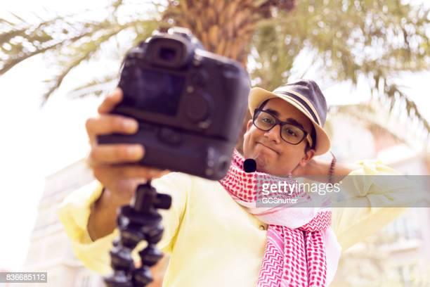 Tiener krassen van de achterkant van zijn nek in onzekerheid tijdens het opnemen van zijn vlog