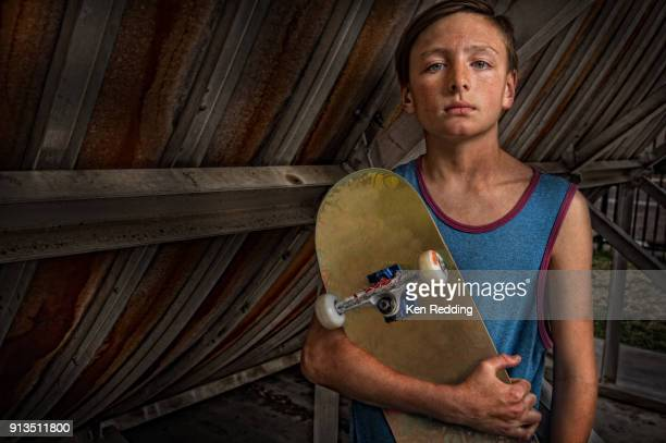 Teen Skate Boarder holding his board