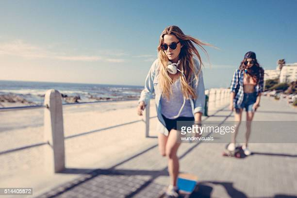 Teen skater girl riding her skateboard along the beachfront