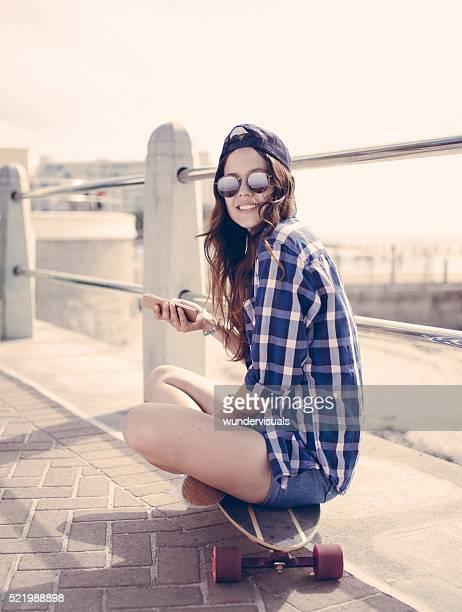 Teen skater girl sitting on her skateboard on a walkway