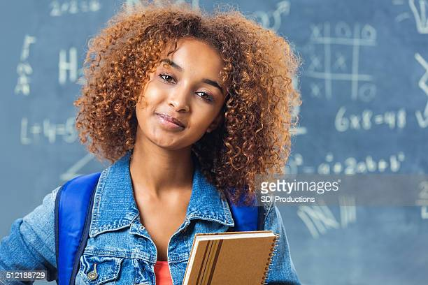 Teen student with curly hair standing in front of blackboard