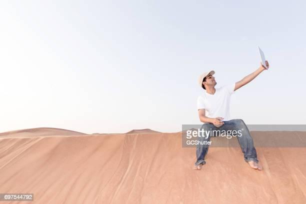 Tiener nemen van een selfie met zijn digitale tablet in de woestijn