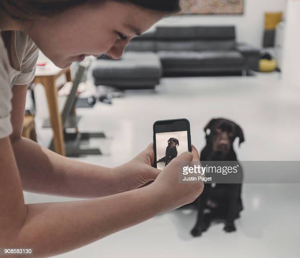 Teen taking photo of dog on smartphone
