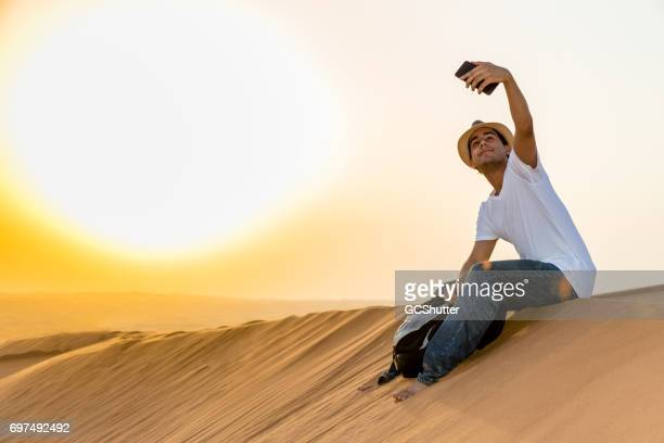 Tiener Selfie te nemen tijdens zijn bezoek aan de duinen of Arabia