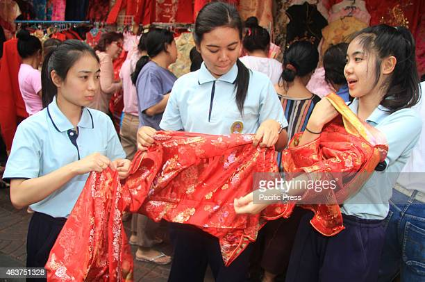 A teen Thai try try to fit on some silk cheongsam in preparation of the Chinese New Year