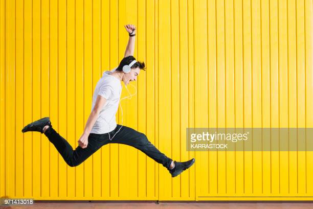 teen with headphones and smartphon listening to music jumping - yellow photos et images de collection