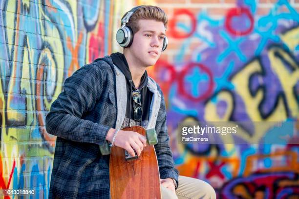 teen with skateboard - hoodie headphones stock pictures, royalty-free photos & images