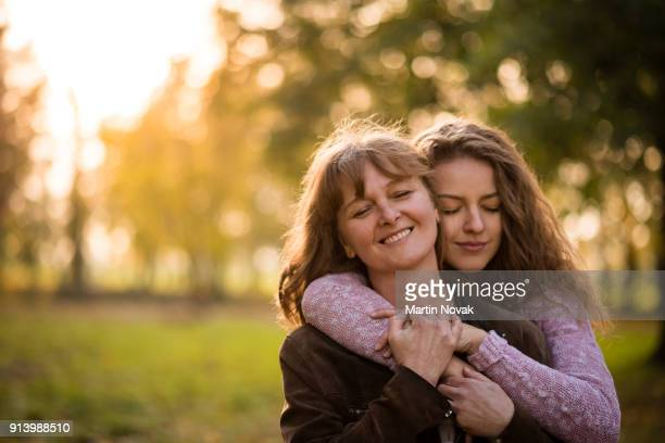 teen woman embracing mother with closed eyes - mamma e figlia foto e immagini stock
