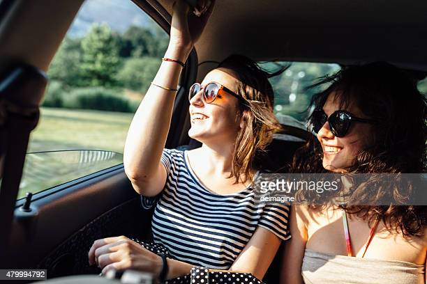 Teen woman friends traveling by car in the summer