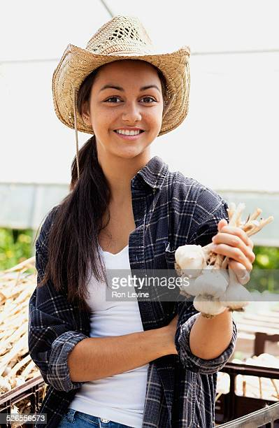 Teen worker on an organic farm holding garlic buds