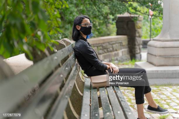 teenage 17-years-old girl wearing face protective mask resting on a bench nearby central park, manhattan, new york. - 16 17 years stock pictures, royalty-free photos & images