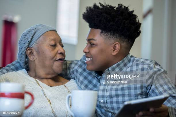 teenage african american boy using digital tablet with arm around grandmother - grandson stock pictures, royalty-free photos & images