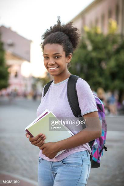 Teenage African girl with books going to school.