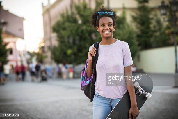 teenage african girl with skateboard and backpack going to school. - puberty girl stock photos and pictures