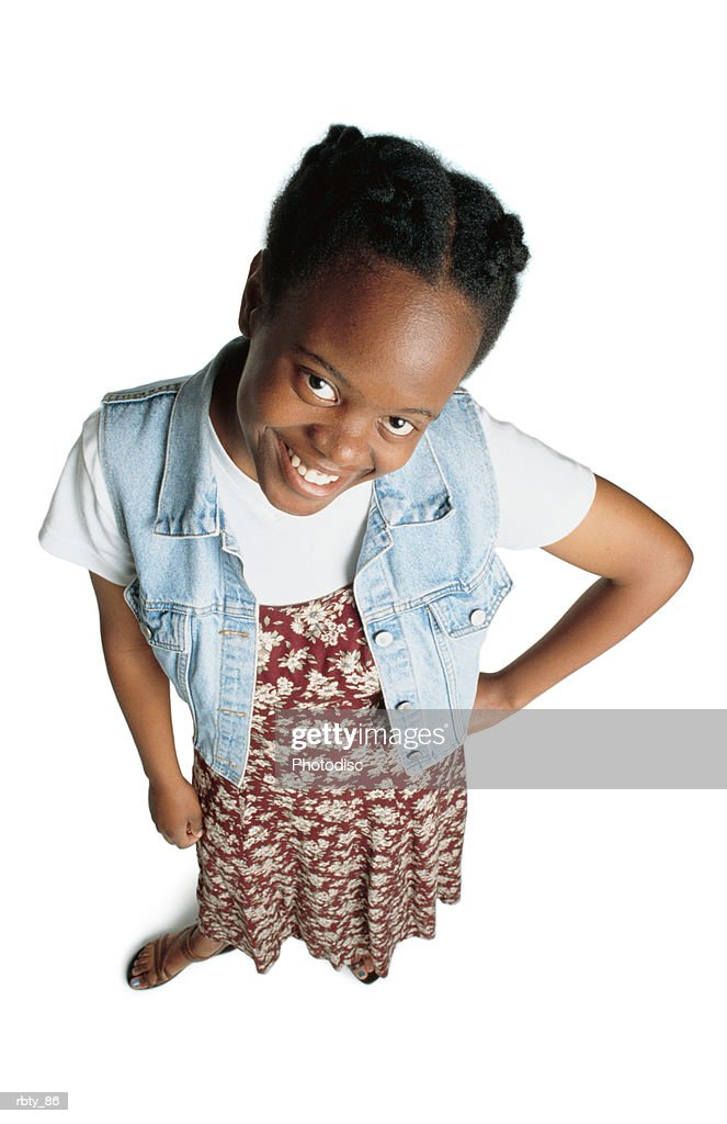 teenage african-american girl wearing a red flower dress with a denim jacket and a white shirt and sandles puts a hand on her hip as she looks up toward the camera and smiles : Foto de stock