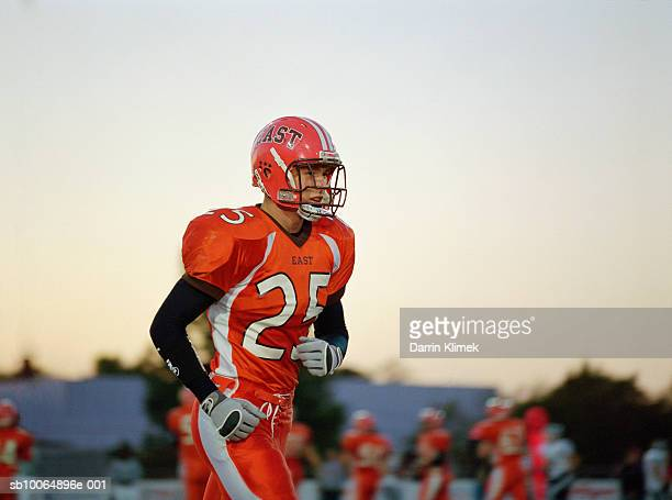 teenage (16-17) american football player running, others in background - american football strip stock pictures, royalty-free photos & images
