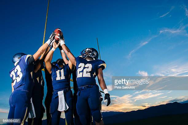 teenage and young male american football team celebrating and holding up ball - team sport stock pictures, royalty-free photos & images