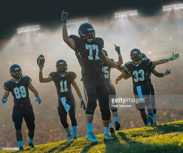 teenage and young male american football team celebrating in stadium - american football strip stock pictures, royalty-free photos & images