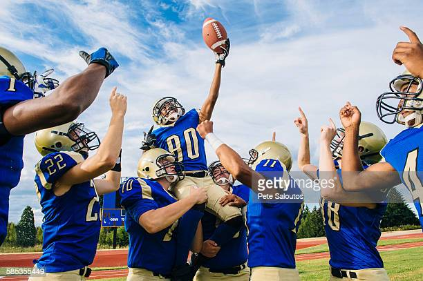 teenage and young male american football team celebrating together on soccer pitch - playing football stock pictures, royalty-free photos & images