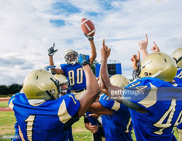 Teenage and young male American football team celebrating victory on soccer pitch
