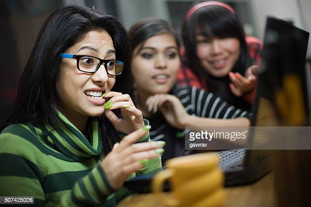 Teenage Asian girl biting fingernail and using laptop with friends.