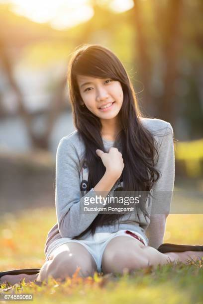 Teenage asian girl sitting on floor in a park