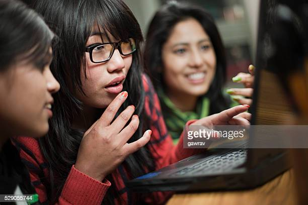 アジアの女の子 10 代の異なる民族ノートパソコンを使うしています。