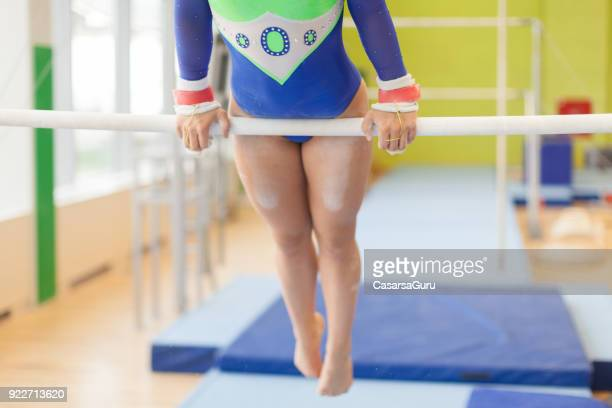 teenage athlete exercising on uneven parallel bars - horizontal bars stock pictures, royalty-free photos & images